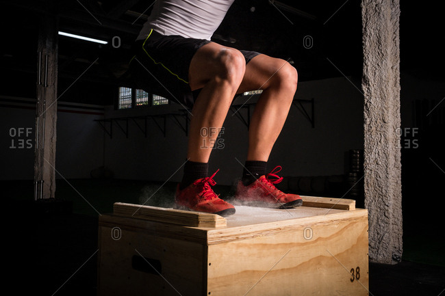 Crop athletic young guy in sportswear jumping on wooden box between chalk dust in gym