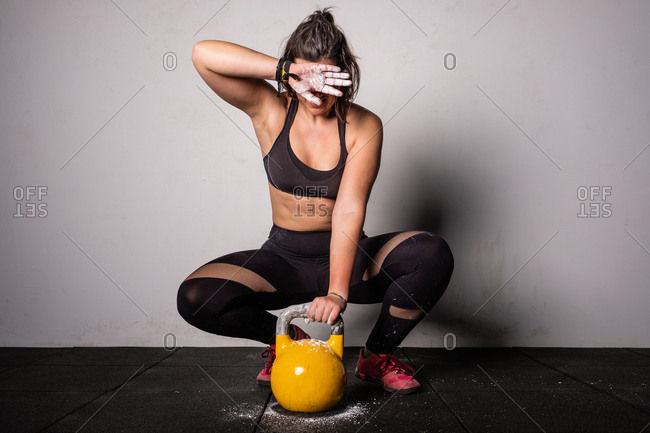athletic young concentrated woman in sportswear upping kettle bell in gym