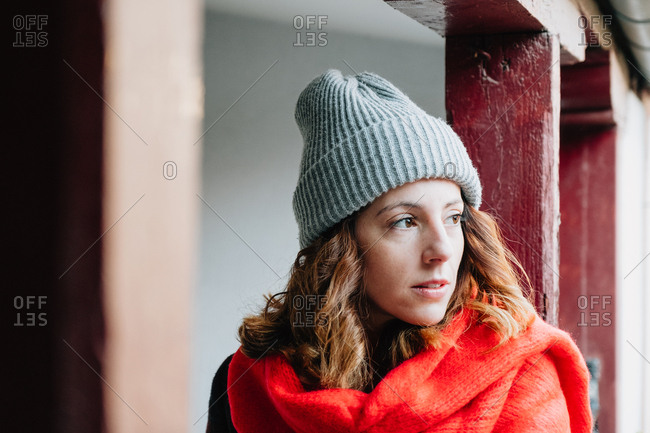 Friendly young lady in winter wear looking away and standing near building
