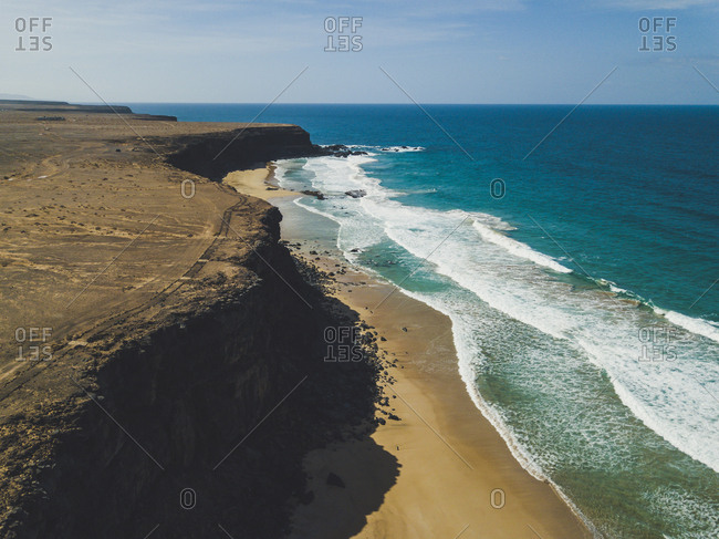 Aerial view of huge cliffs on wild coast of ocean with white waves running on sandy beach, Spain