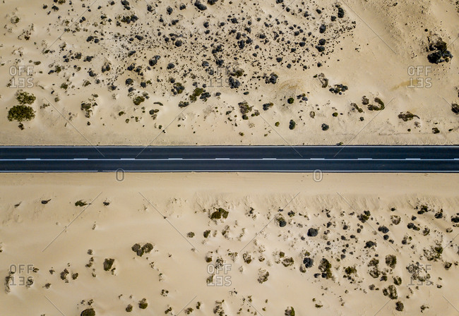 Drone view from above of straight line of paved road in dry sandy land of desert, Spain