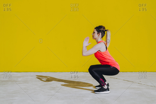 Young lady in sportswear doing squad exercises near yellow wall