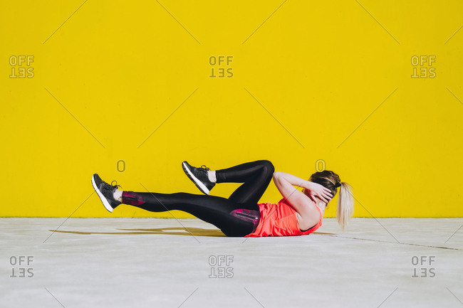 Young lady in sportswear doing sit ups exercises on floor near yellow wall