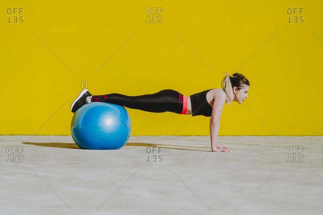 Side view of young lady in sportswear doing plank with legs on big fitball on yellow background