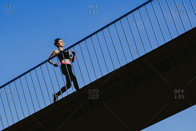 Young lady in sportswear running on footpath of a bridge in sunny weather with blue heaven