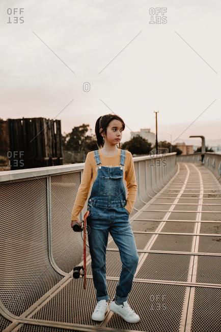 Girl with skateboard on walkway