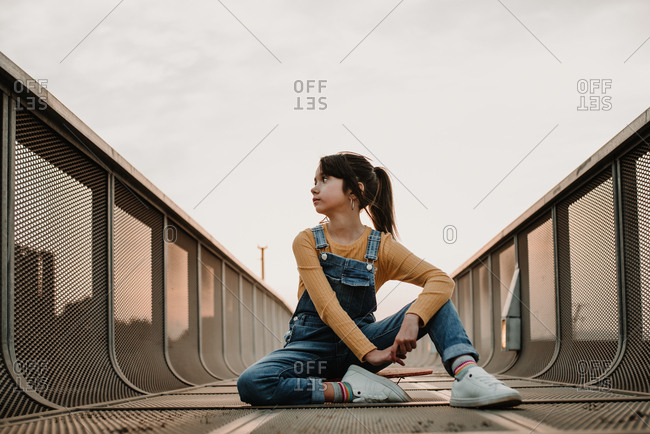 Girl sitting on skateboard on walkway