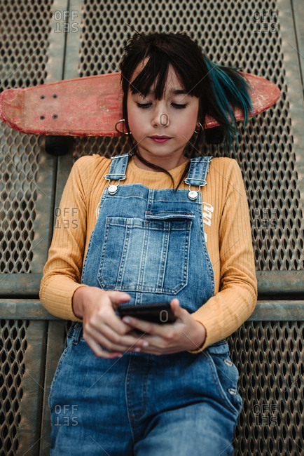 From above stylish teen in jean overall with head on skateboard using mobile phone and lying on footpath