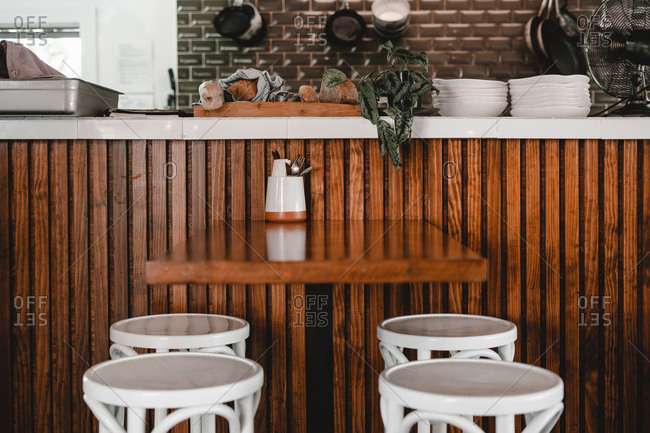 Stools near table and wooden bar counter with plates in cafe
