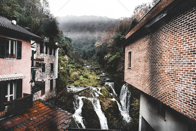 Picturesque view of river running between hills and waterfall near old brick houses of small town in Italy