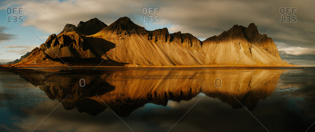 Panoramic view of amazing cliff mountain reflecting in tranquil water, Iceland