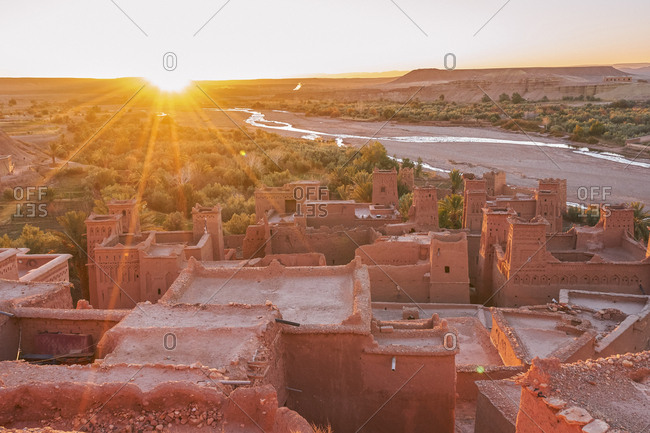 From above old town with stone constructions near narrow river between desert and beautiful heaven with clouds in Marrakesh, Morocco