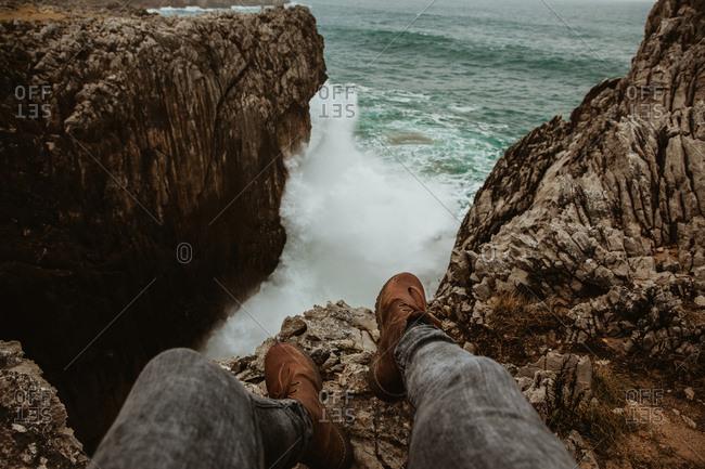 Crop legs of human sitting on top of stone near stormy sea in Bufones de Pria, Asturias, Spain