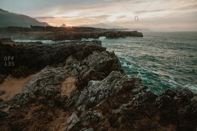 top of stone near stormy sea in Bufones de Pria, Asturias, Spain