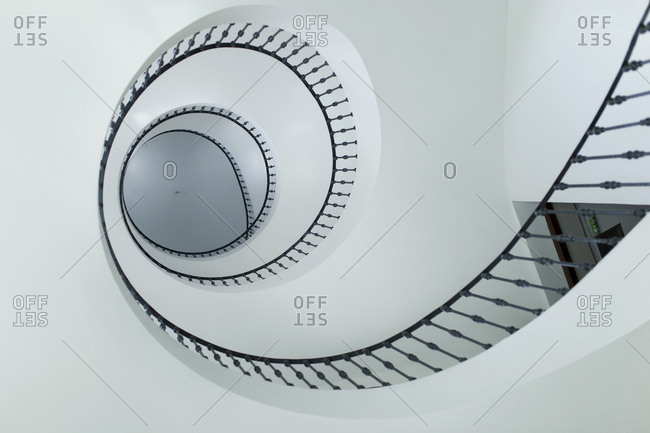 From below modern spiral stairs with black railing indoors