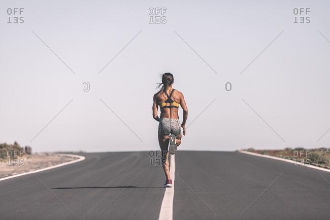 Ethnic sportswoman running on desert road