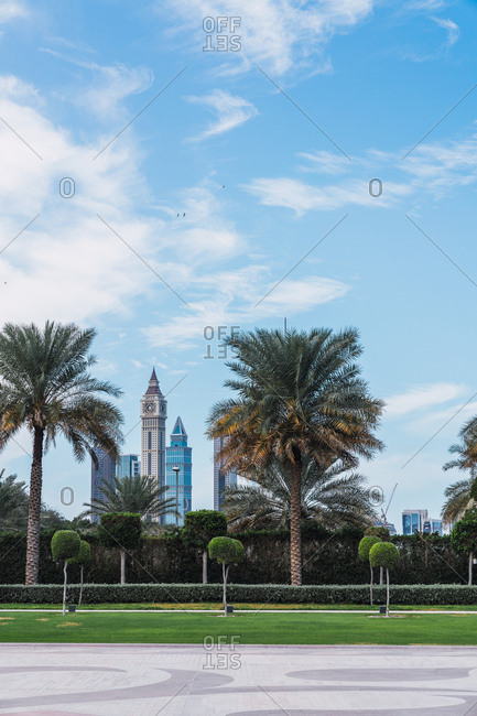 Beautiful view of blue cloudy sky over wonderful city park with exotic palms on sunny day in Dubai