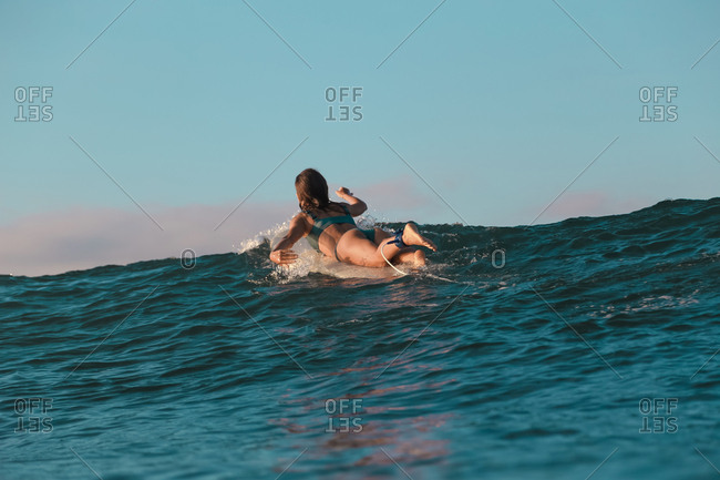 back view of cheerful female floating on surf board between water of sea and blue heaven on Bali, Indonesia