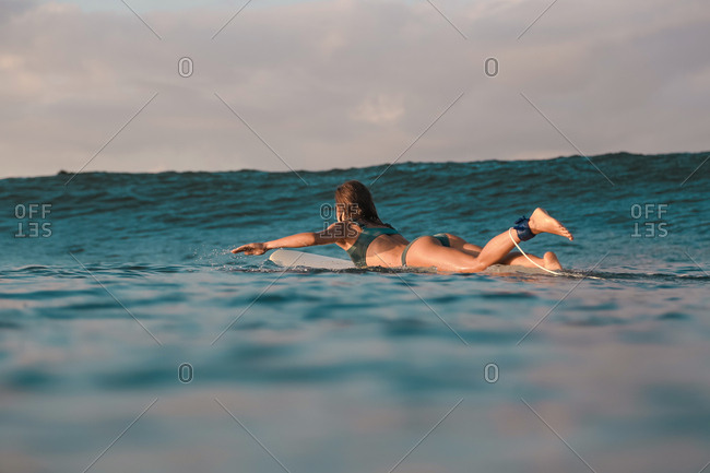 Side view of cheerful female floating on surf board between water of sea and blue heaven on Bali, Indonesia