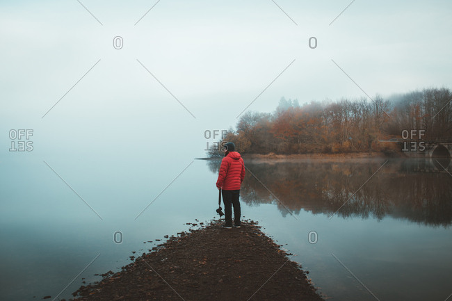 Back view of photographer in red coat standing on coast of tranquil lake in mist
