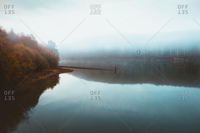 Beautiful tranquil lake in fog