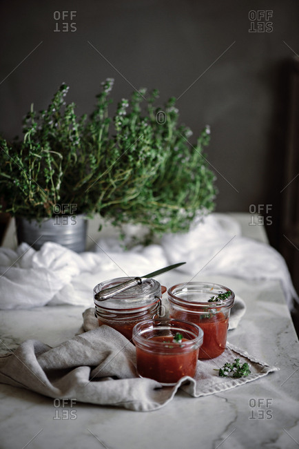 Little jars with delicious fresh tomatoes homemade jam near herbs and napkin on table on blurred background