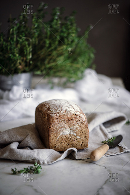 Delicious fresh aromatic rye bread on napkin near knife on blurred background