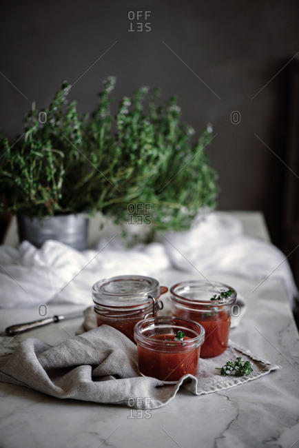 Top view of little jars with delicious fresh tomatoes homemade jam near herbs and napkin on table on blurred background