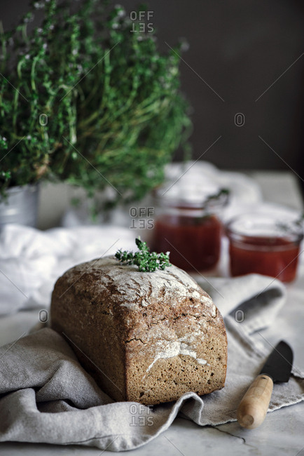 Delicious fresh aromatic rye bread on napkin near knife and cans with tomatoes homemade jam on blurred background