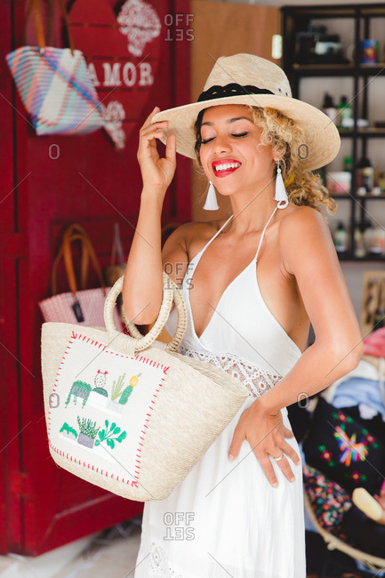 Beautiful stylish black young woman with hat and handbag shopping in Mexico