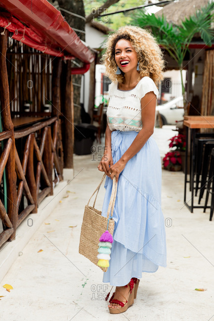 Beautiful stylish black young woman with curly hair and handbag between construction in Mexico