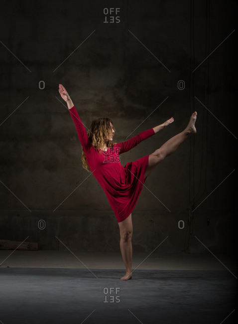 Young slim ballerina in red dress upping leg and hands in dark room