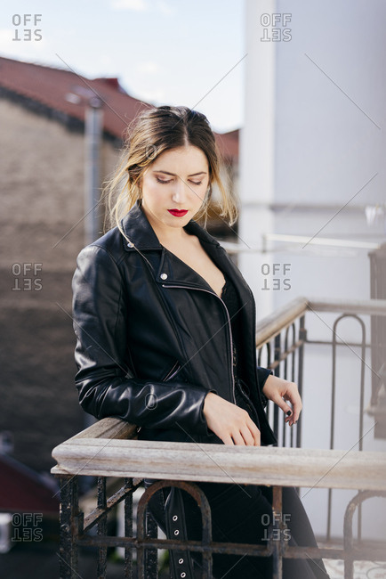 Beautiful young female in trendy outfit keeping closed eyes while standing on apartment balcony against amazing town