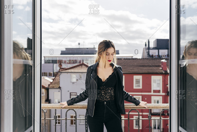Beautiful young female in trendy outfit keeping closed eyes while standing on apartment balcony against amazing town and cloudy sky