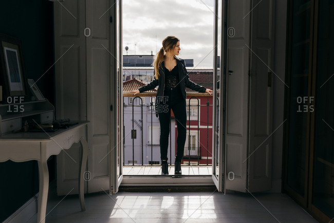 Beautiful young female in trendy outfit looking away while standing on apartment balcony against amazing town and cloudy sky