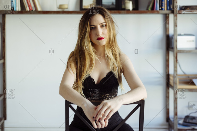 Pretty young female in black lace bra looking at camera while sitting on comfortable chair in stylish room at home