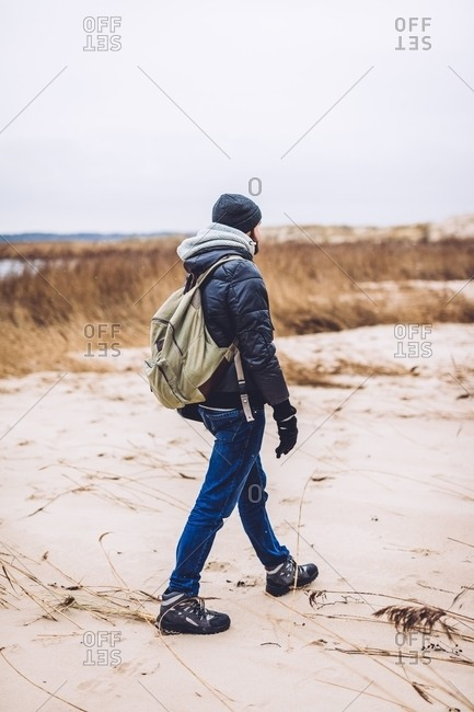 Back view of guy in coat and hat with backpack going on sand land between dry grass
