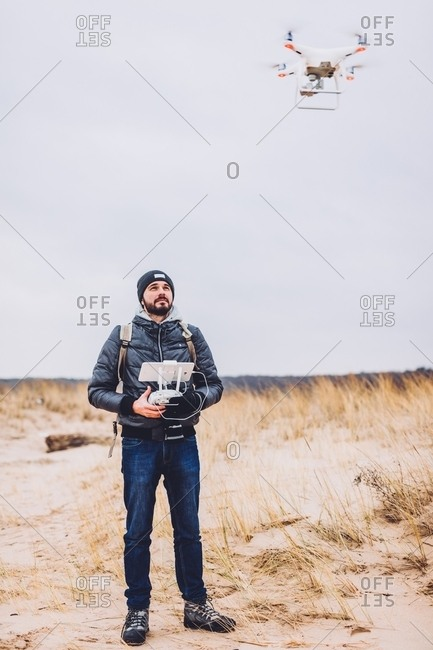 Young guy with remote control operating flying drone on hill between trees on blurred background