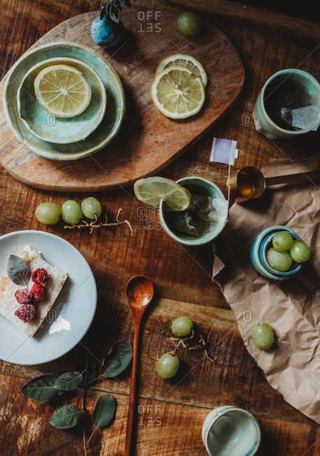 From above of beautiful ceramic plates and cups with slices of lemon and grapes in composition on wooden table
