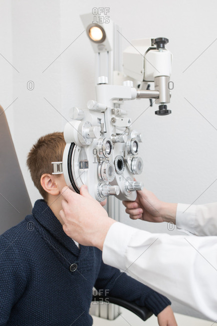 Optician testing a boy's eyes with optometry devices