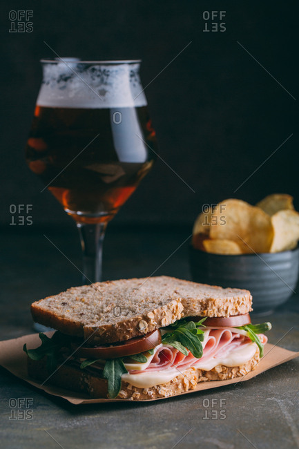 Delicious sandwich with ham, cheese, lettuce and tomato with a glass of beer and chips on dark and grunge background