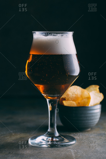 Glass of beer and chips on dark and grunge background