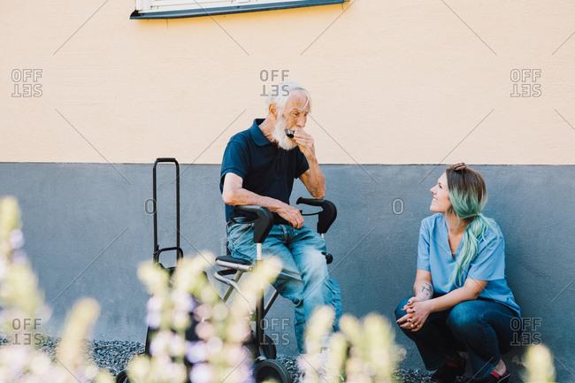 Smiling female nurse looking at senior man playing harmonica against wall at back yard