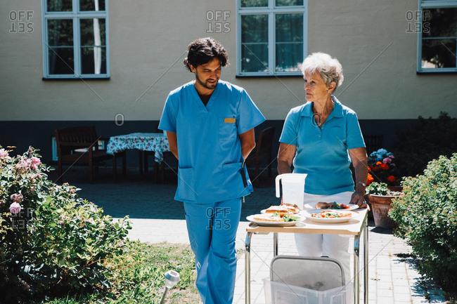 Male nurse walking with senior woman pushing food cart against nursing home