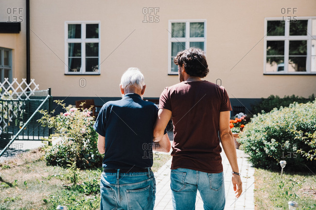 Rear view of male caretaker walking arm in arm with senior man at nursing home