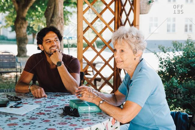 Smiling male caretaker looking at senior woman sitting with gift at back yard