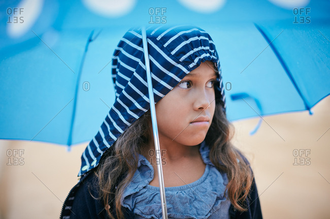 Girl with umbrella looking away during rainy season