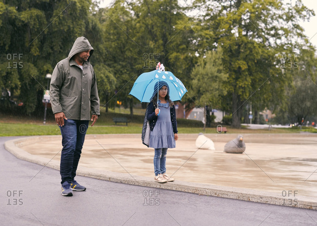 Full length of father looking at daughter with umbrella while standing in park during rainfall