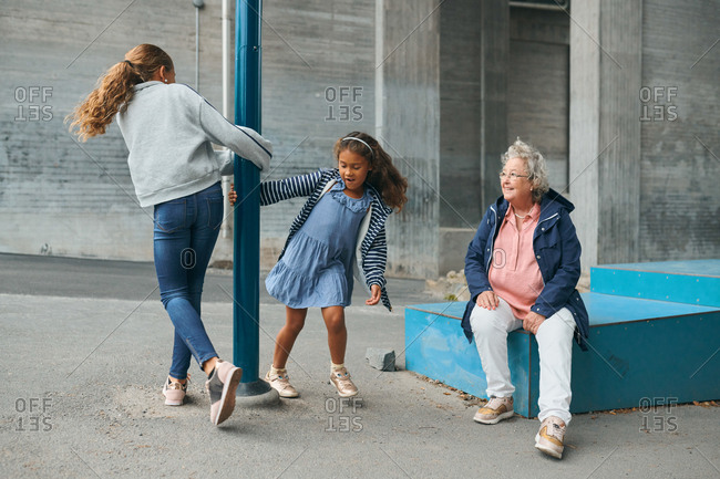Smiling grandmother looking at playful granddaughters spinning around pole at playground