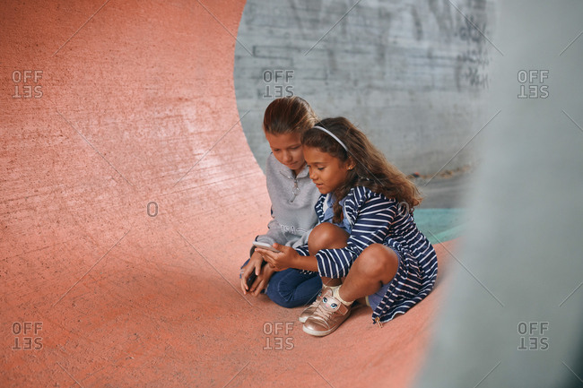 Sisters using mobile phone while sitting in tunnel at playground